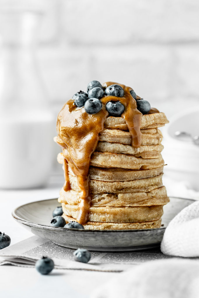 Stack of fluffy sourdough pancakes with caramel sauce and berries